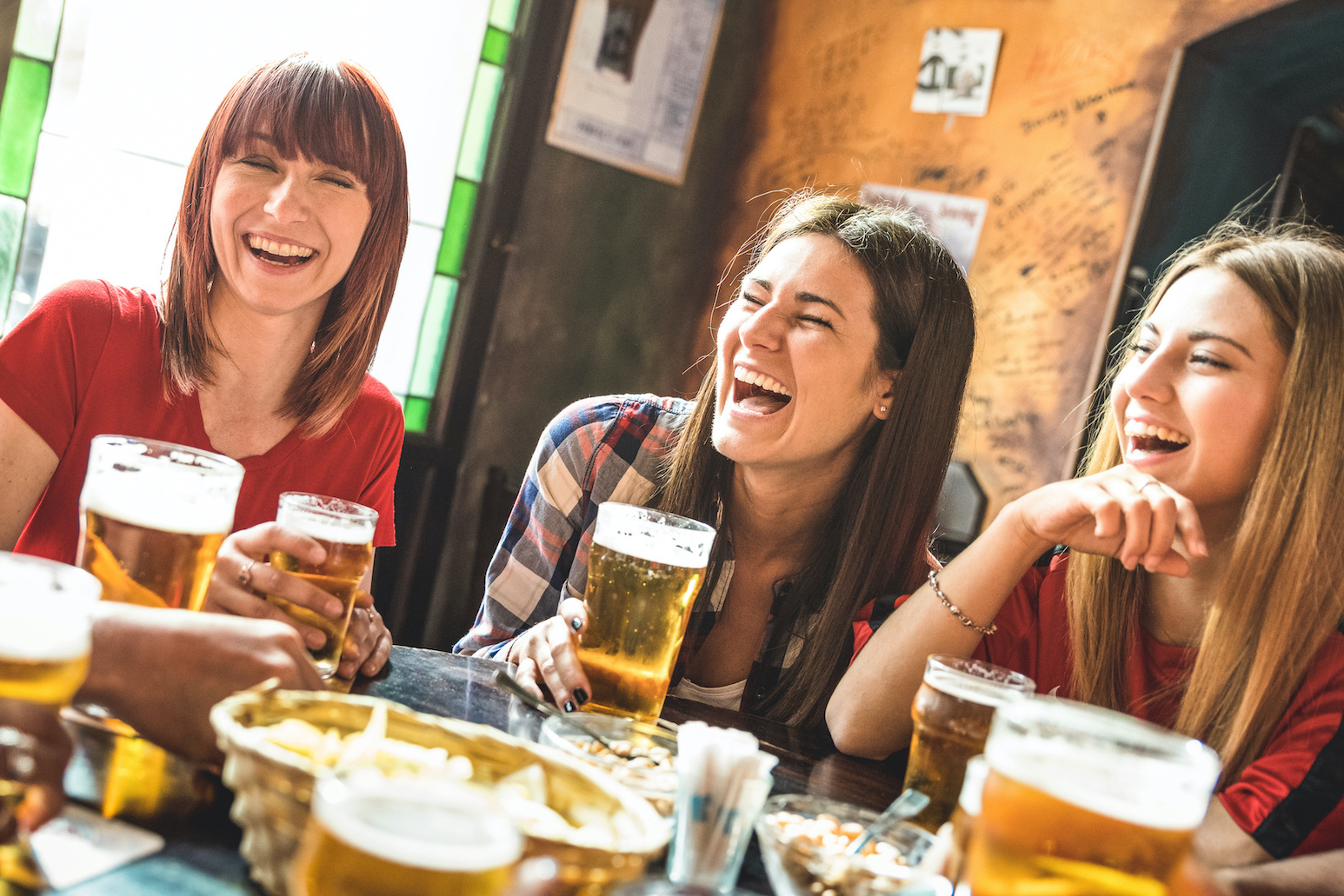 Young women laughing and drinking beer