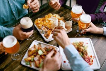 Men Drinking Beer And Eating Snacks, Tasty Food Closeup In Pub Restaurant. High Resolution.