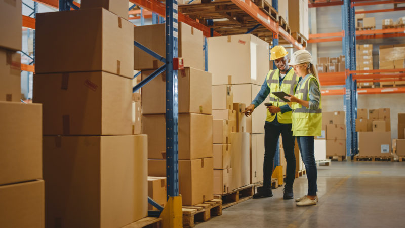 Retail Warehouse full of Shelves with Goods in Cardboard Boxes, Male Worker and Female Supervisor Holding Digital Tablet Discuss Product Delivery while Scanning Packages. Distribution Logistics Center