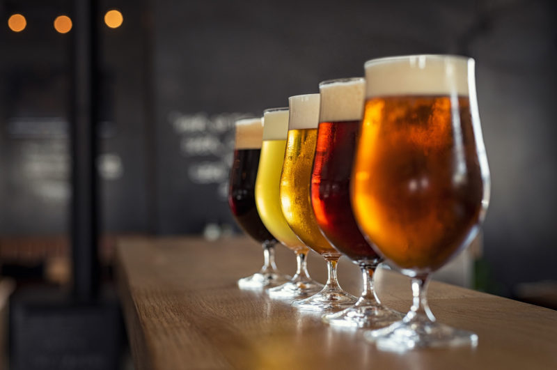 different colored beer in glasses on bar