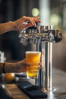 hands pouring beer from beer tap